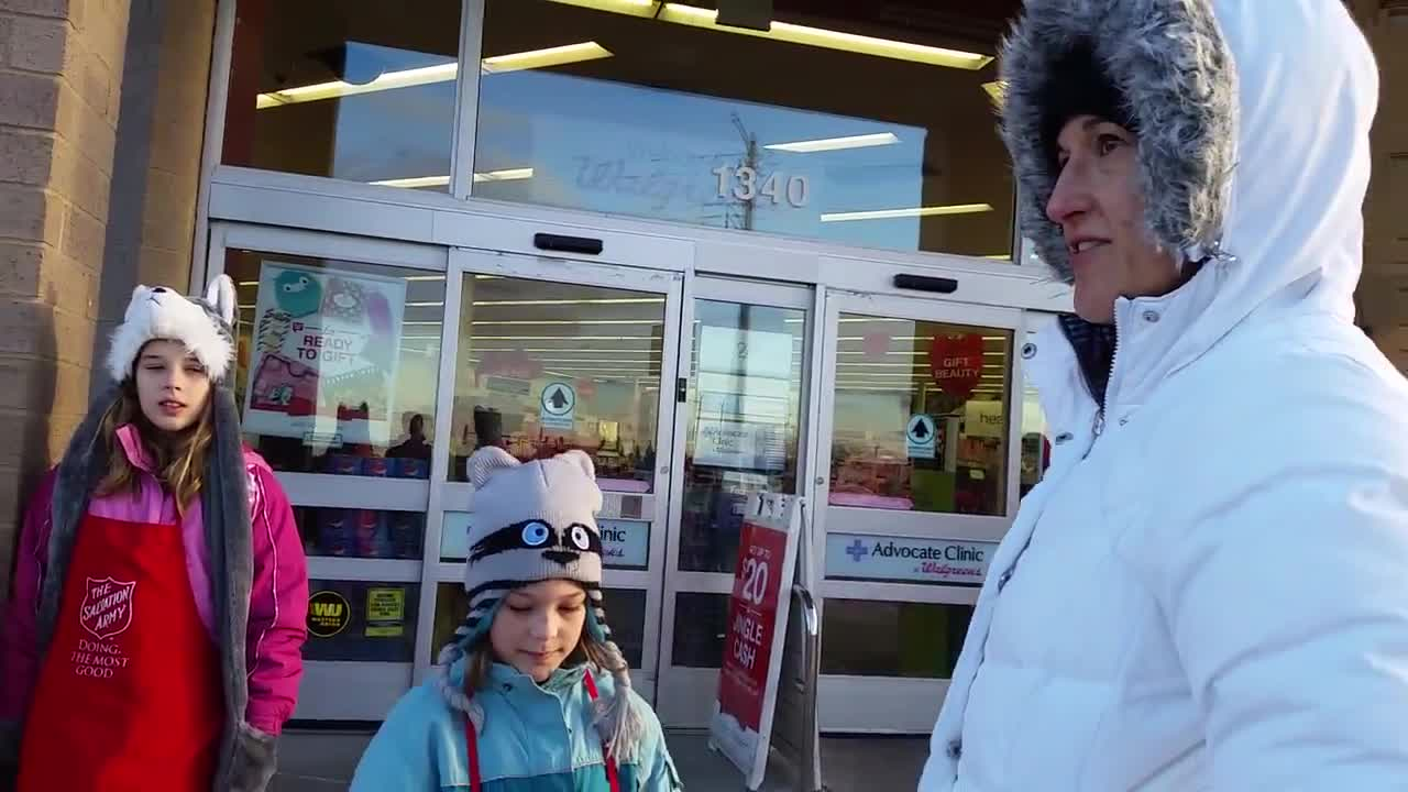 The Kaczor family mans a red kettle outside Walgreen's in Sycamore for The Salvation Army.