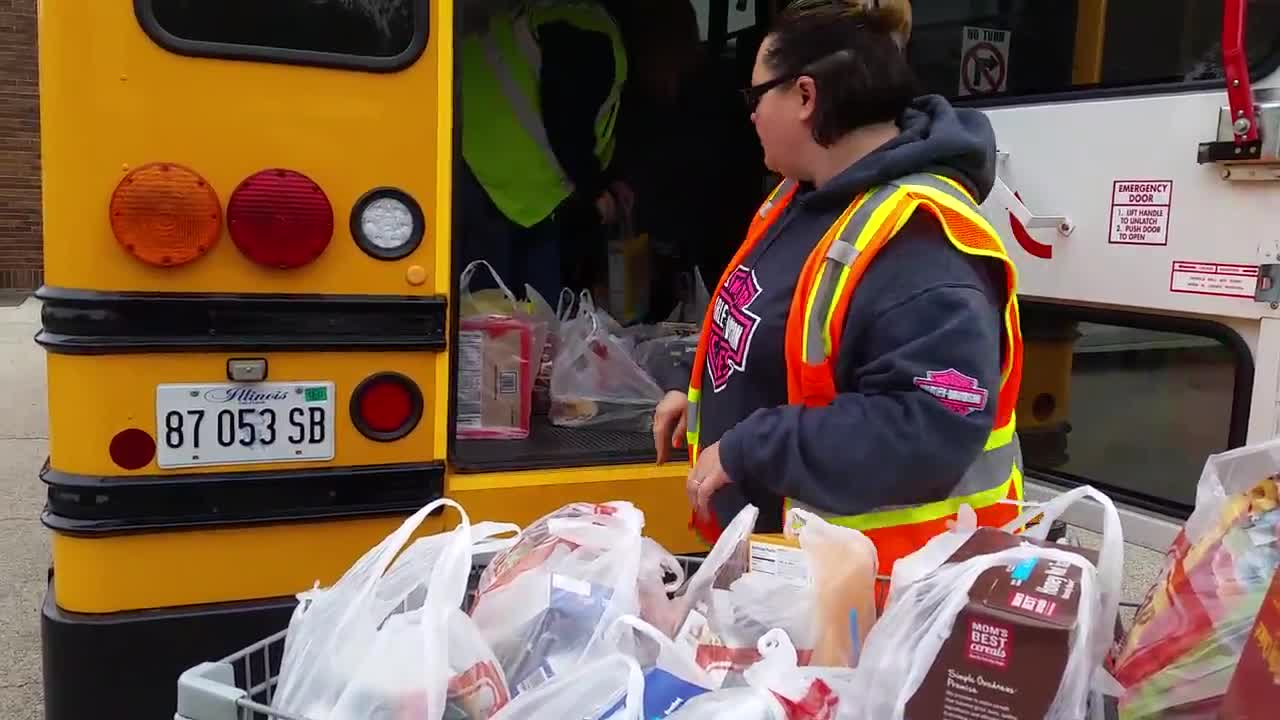 Denis Cagle and Christine Urich, bus drivers for First Student, unload bags of nonperishable food from a bus at The Salvation Army.